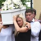 Ronan McGavigan's parents Laura and John carry their little boy's coffin at St Columb's Church Long Tower in Derry