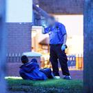 Police officers at the scene in the Laurelbank area of west Belfast on Sunday, after a man was shot in a paramilitary-style attack