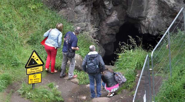 Visitors to Dunluce Castle look into the cave from which a man had to be rescued on Sunday