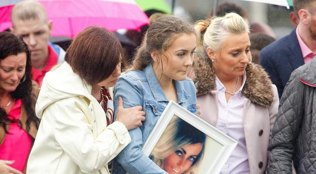 Cliodhan McStravick carrying a picture of her mum Michelle McStravick yesterday at her funeral at St MacNissi's Church in Randalstown