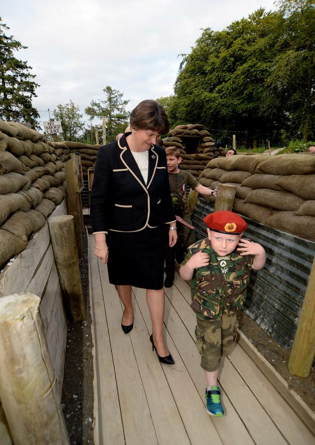 Northern Ireland First Minister Arlene Foster is led by Jonathan Smith (5) from Arva, Co Cavan, through the WWI trench
