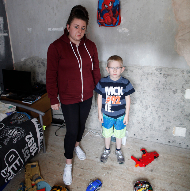 Rachelle Austin and Logan in his bedroom, which was left with bare walls after work to eradicate damp was not finished