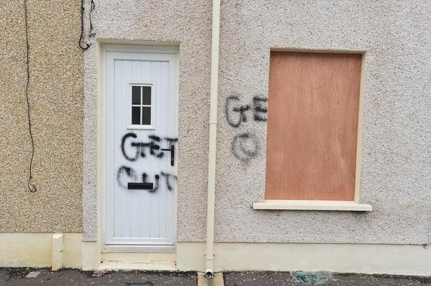 Graffiti is painted over the door of the house