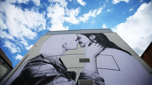 Giant mural in Belfast of two women kissing by street artist Joe Caslin