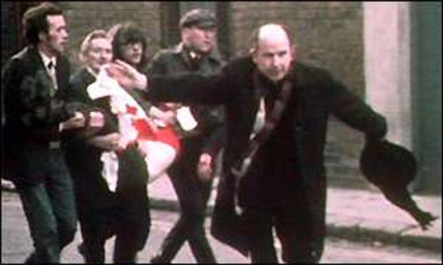 Fr Edward Daly waves a white handkerchief as the body of Bloody Sunday victim Jackie Duddy is carried along Chamberlain Street, Derry