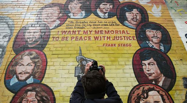 A tourist takes a photo of a mural painted on the peace wall on Divis Street, Belfast.