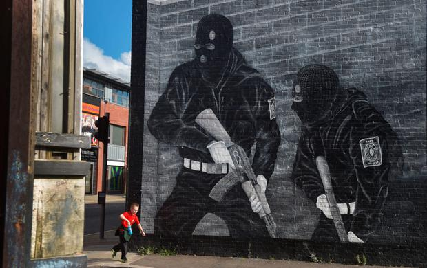 A young boy plays near a terrorist mural in east Belfast
