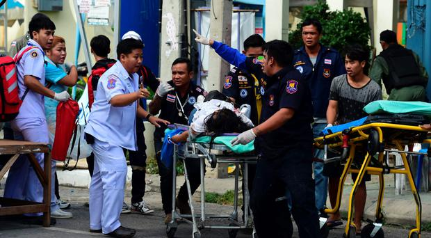 Thai rescue workers attend to an injured victim after a bomb exploded in Hua Hin