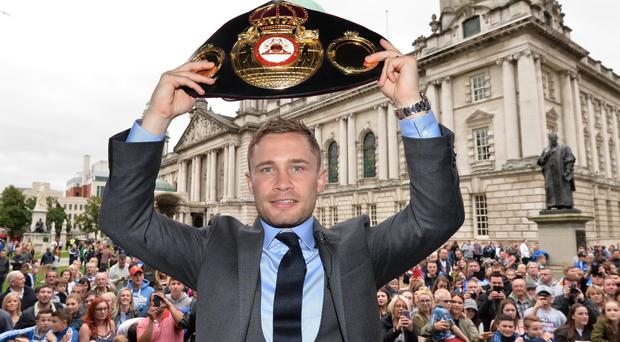 Carl Frampton holds aloft his title belt as fans welcome him at Belfast City Hall last night