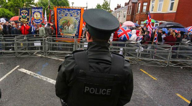 A police officer watches as the Orange parade meets the barricade at Woodvale in 2014