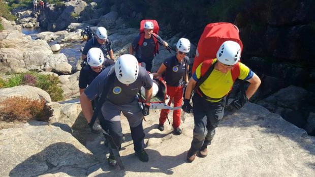 The Mourne Mountain Rescue Team carrying the woman to safety after she fell and injured herself as she walked on rocks on the southern side of the Bloody Bridge River