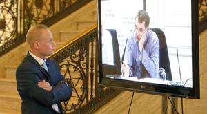 Jamie Bryson watches Sinn Fein's Daithi McKay on television before appearing at Stormont's Nama inquiry