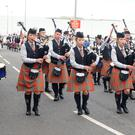 At the North West Pipe Band Championships in Portrush, Pipe Major David Hawthorne (left) of Whitewater Pipe Band and his identical twin daughters Faith and Grace parade through the streets of the seaside town on Saturday