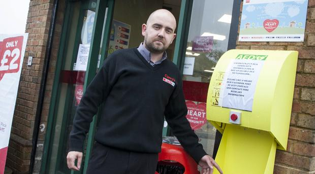 Richard Campbell, proprietor of the Spar shop at Church Meadow, points to the damaged defibrillator box