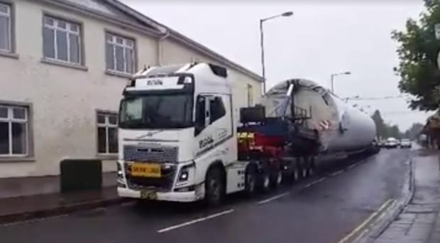 The lorry loaded with a huge wind turbine makes its way into the village