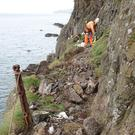 Specialists carry out painstaking work to ensure that loose rocks are removed along the route of the Gobbins walkway