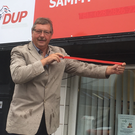 Sammy Wilson uses red tape to cover up part of his office sign