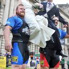 Groom Brian Newman and bride Yvonne with strongmen Ben Thompson (left) and Richard Bessant outside City Hall yesterday