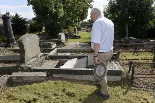 A man inspects his father's grave after the vandalism