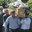 David Sheridan carries his son Daniel's coffin after the funeral at St Anne's Church, Bohernabreena