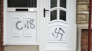 Racist graffiti, including a swastika, daubed on the door of a house in the Orangefield area of Co Armagh (PSNI/PA)