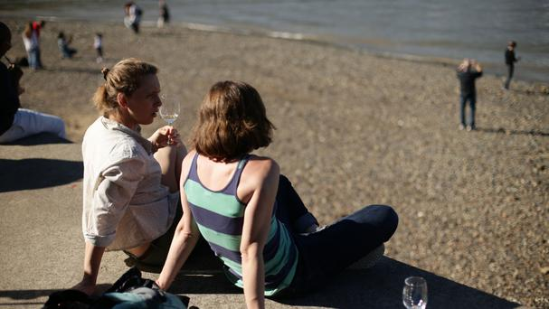 People enjoy the warm weather on the banks of the River Thames, Bankside, London.
