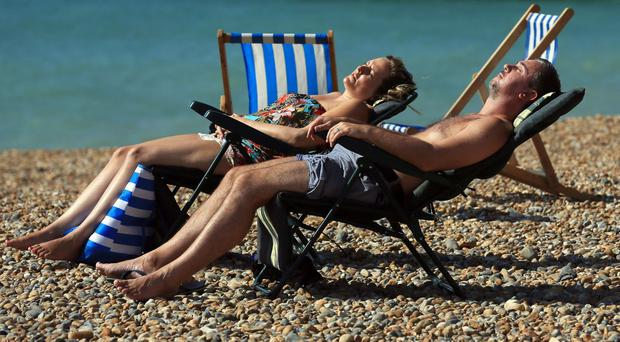 A couple enjoy the warm weather on the beach in Brighton.