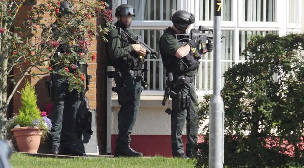 Armed police point their rifles at a house at Knockantern Grove in August
