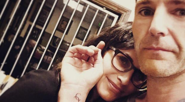 Johnny McDaid showing off his tattoo with Courteney Cox
