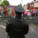 A police officer looks on as a loyalist parade marches to Woodvade Parade