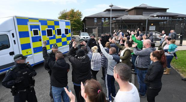 Family, friends and supporters cheer at a police cell van carrying the four men, including Shea Reynolds, who were charged in 2016