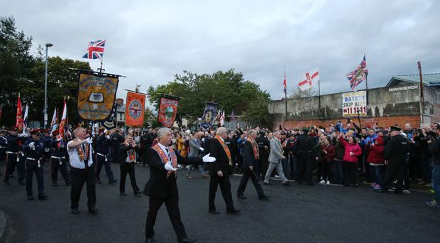 Loyalists cheer as the Orange Order parade passes along the Crumlin Road
