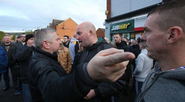 Damien Fennell, a spokesman for the Greater Ardoyne Residents' Collective, argues with Father Gary Donegan, left