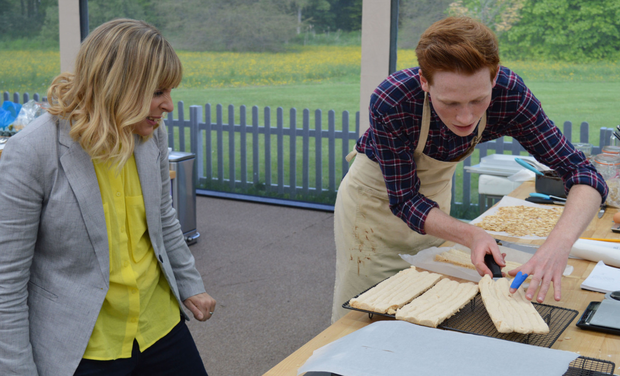Mel Giedroyc watches as Andrew cuts his meringue layer