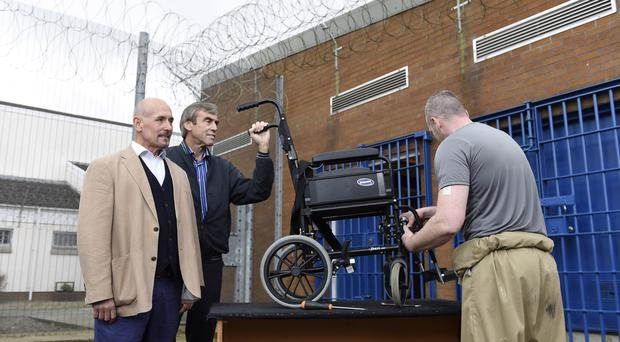 Robert Jones and Ray Allen from charity, Medaid4kids, watch as prisoners in Maghaberry restore wheelchairs to be shipped abroad