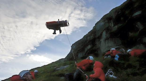 The injured man is helped to safety by the mountain rescue team