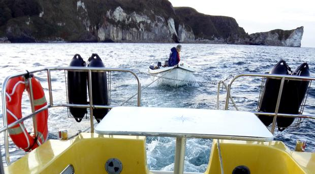 The Rev Harold Good in the boat being pulled to shore at Ballycastle