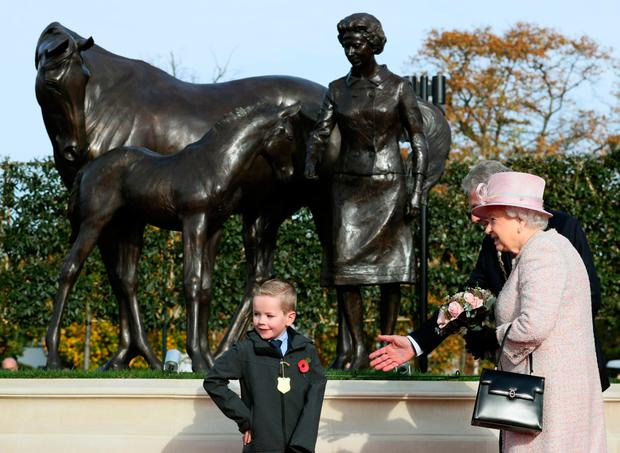 The Queen receives flowers from little Thomas Cotton (8) at Newmarket