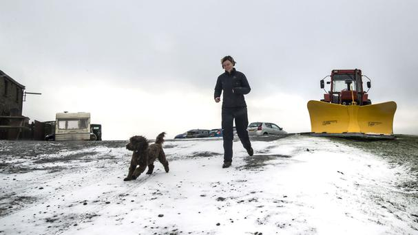 A woman walks her dog following a light dusting of snow at Tan Hill in North Yorkshire