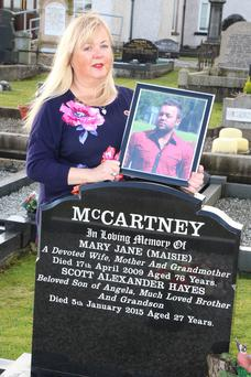 Angela Knott with a picture of her late son Scott Alexander Hayes at his graveside
