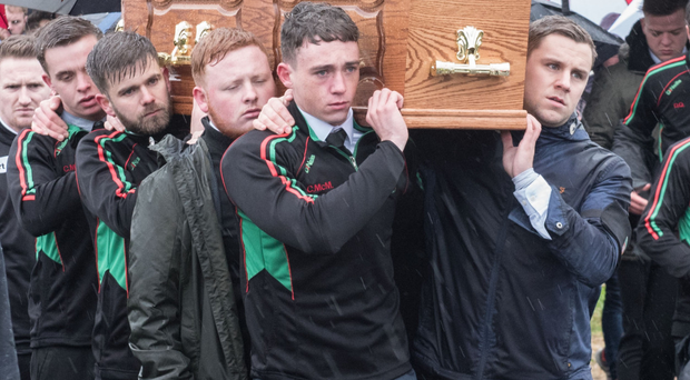 The coffin of Kevin King is carried by team-mates from St Mary's