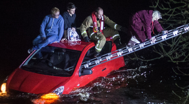 Three people are rescued after they became trapped on the roof of their car in the River Bush in Stranocum last night