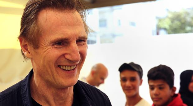 Actor Liam Neeson listens to stories from Syrian and Jordanian students at a community centre in a working-class neighbourhood of Amman, Jordan (AP)