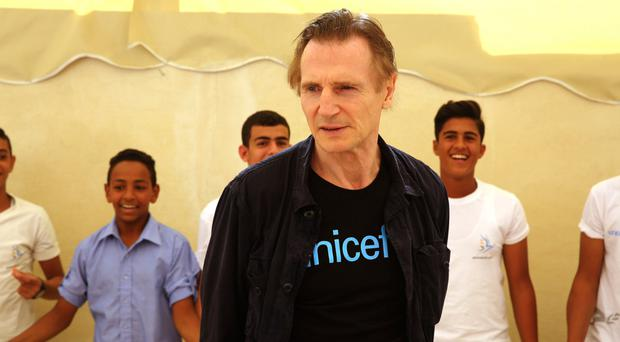 Liam Neeson with Syrian and Jordanian students at a community centre in a working-class neighbourhood of Amman, Jordan