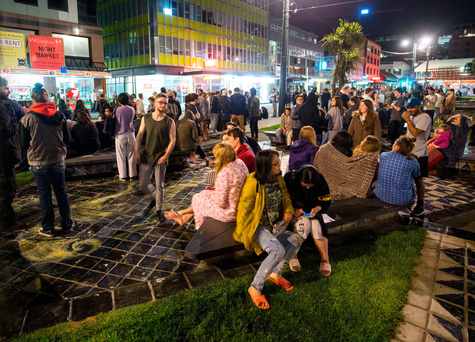 People wait in Wellington's Te Aro Park after being evacuated from nearby buildings following the earthquake, which caused significant damage