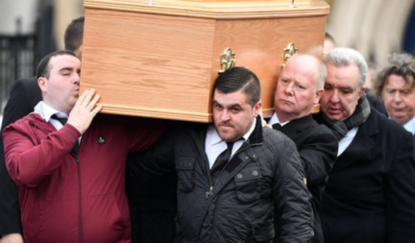 Family and friends at the funeral of James Hughes, including his brother Michael, back right, help carry his coffin at St Peter's in Belfast yesterday