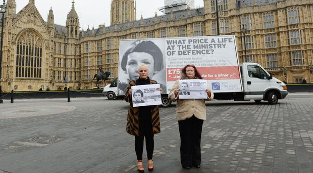 Christine Quinn, left, and Roberta O'Neil, the daughters of Christopher Quinn, in front of a poster in Westminster, London