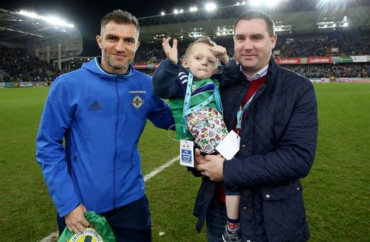 Little Zak on pitch at Windsor last night with his dad Gareth and NI star Aaron Hughes