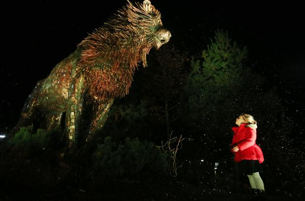 Five-year-old Annie-Mae McCracken stands beside Maurice Harron's sculpture of Aslan in CS Lewis Square