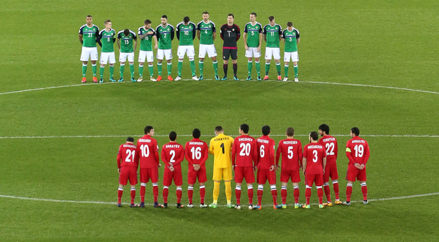 The teams observe a minute's silence in front of the poppy mosaic at Windsor Park